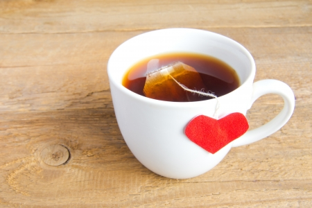 White cup of tea with red heart shaped label on teabag on wooden background (surface). Love and care concept. photo