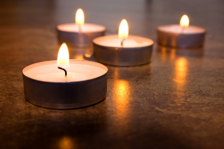 memorial candle: Four burning candles on marble surface (background) with reflection. Close up scene, copy space. Concept of memory, meditation, relaxation.