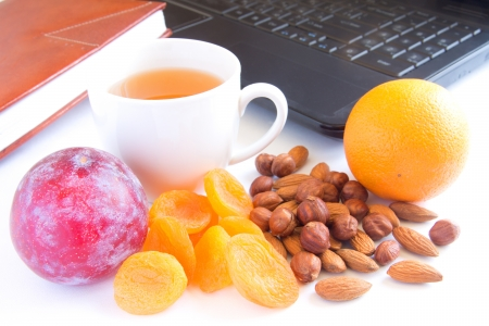 Healthy quick snack (lunch) in office. Cup of tea, fruits and nuts.