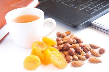 Healthy quick snack (lunch) in office. Cup of tea, dry apricots (fruits) and nuts.