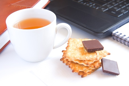 Healthy quick snack (lunch, break) in office. Cup of tea, cookies (biscuits) and chocolate on white desk with computer.