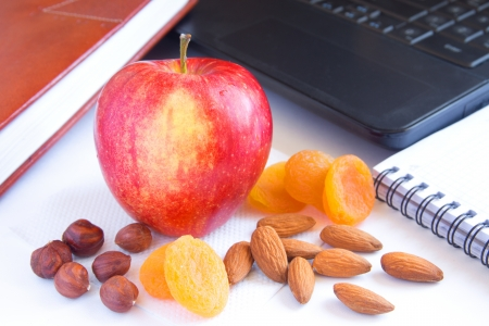 dry fruits: Healthy quick snack (lunch) in office. Red apple, dry fruits (apricots) and nuts on desk with computer and planner.