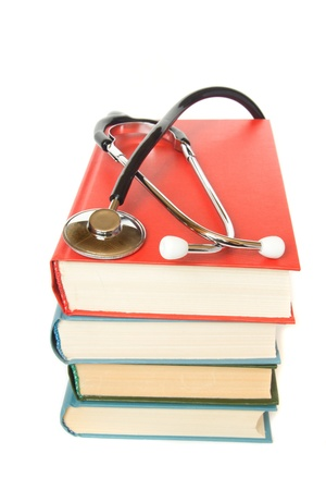 stethoscope and  stack of books close up isolated on white background. Medical professional education and information concept.  photo