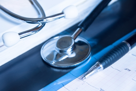 screening: Stethoscope, pen on x-ray and electrocardiogram chart  Medical concept for cardiology, diagnostic, screening, examination  Copy space  Stock Photo