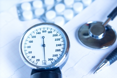 hypotension: Stethoscope, blood pressure monitor close up, pills and pen on electrocardiogram chart  Medical concept for cardiology, examination, screening, blood pressure