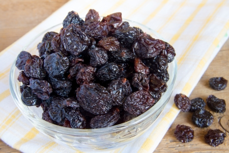 Raisin in glass bowl over wooden background (surface) close up.
