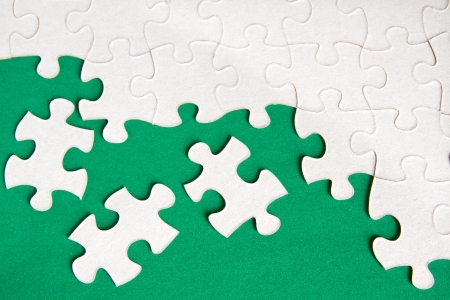 oal: Puzzle pieces on green background close up.  Stock Photo