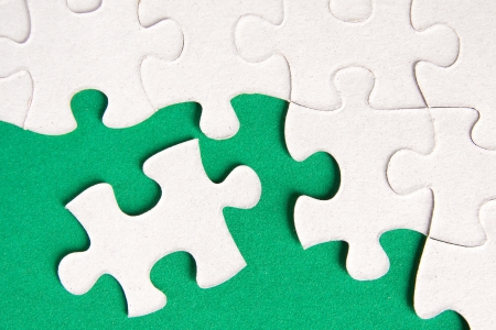 Puzzle pieces on green background close up.  Stock Photo