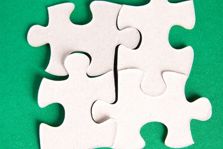 oal: Puzzle four pieces on green background close up.  Stock Photo
