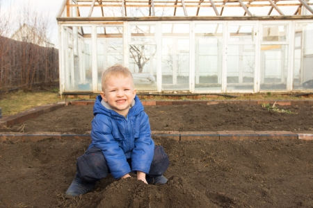 Happy smiling joyful child (boy) digging soil, working in spring garden in village photo