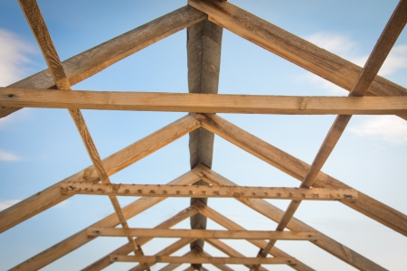 Construction of roof, wooden pine symmetric skeleton and blue sky. photo