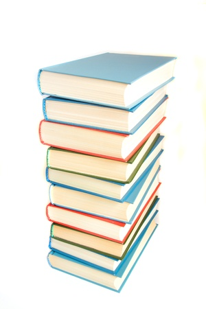 stack of hard covered multicolored books isolated over white stock