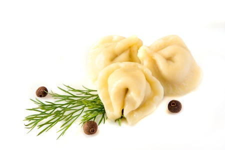 Meat dumplings (pelmeni) with dill (fennel) and pepper isolated on a white background, close up.