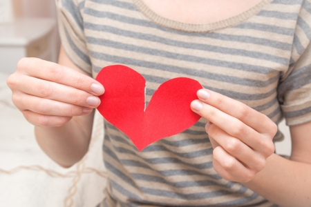 Break red heart in beautiful female hands (fingers) in bedroom. Conflict in couple, problems, divorce and pain concept. Stock Photo