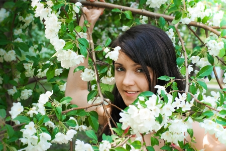 Beautiful young sensual brunette smiling woman (girl) near blooming apple tree. Srping concept. photo