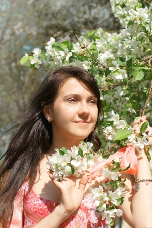 Beautiful young brunette smiling woman  near blooming apple tree. photo