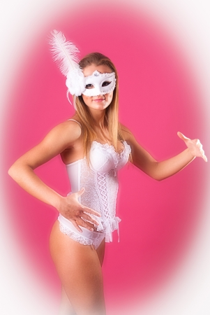 Beautiful sexy young woman in white mask and lingerie posing like a doll (dummy) over pink background. photo