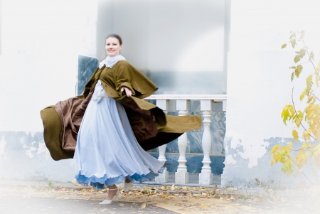 poetic: Retro style beautiful sensual young woman wearing vintage long coat whirling in dance. Poetic romantic mood. Stock Photo
