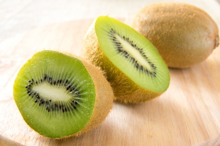 Kiwi halfs and whole close up on wooden background (table) horizontal photo
