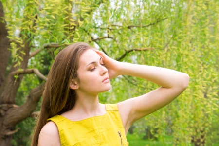 Beautiful young pretty sensual woman in yellow dress outdoor portrait in spring park near blossoming willow