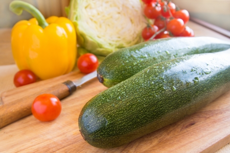 Green ripe zucchini on a wooden background with different vegetables and knife