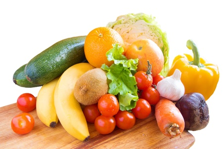 Healthy fresh vegetables and fruits ingredients for cooking in rustic setting on wooden background isolaned on white