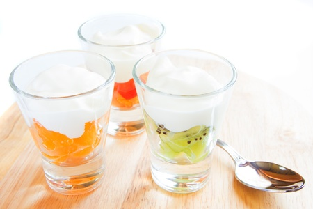 Three fresh yogurt with fruits in glass beaker on wooden cutboard isolated on white closeup, horizontal, copy space