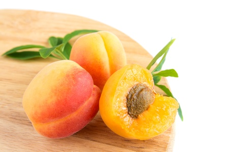 Apricots (whole and part) with leaves over wooden board isolated on white background close up photo