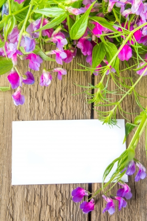 Violet wild spring flowers and white blank card with sample text over rustic wooden background (texture, surface) vertical, close up Stock Photo - 19988960