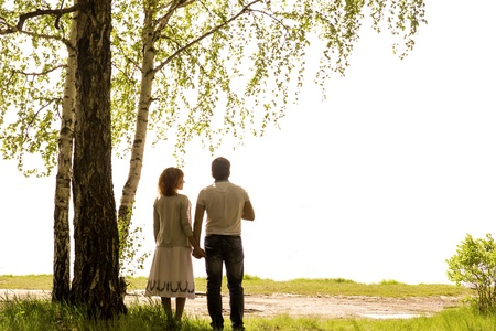 Happy young couple holding hands under birch tree isolated on white background