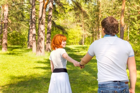 Happy Young Couple in Park having fun together, holding hands photo