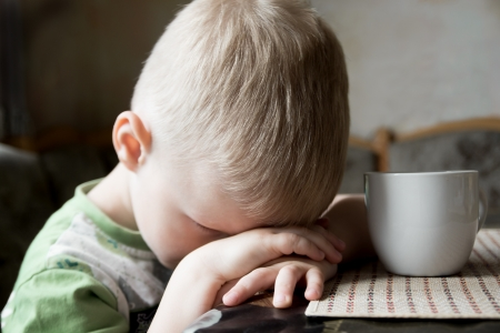 Sad upset tired worried little child (boy) lying on his hands close up portrait Stock Photo