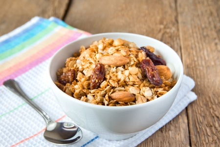 delicious and healthy wholegrain muesli breakfast, with lots of dry fruits, nuts and grains close up, horizontal, on wooden table with spoon
