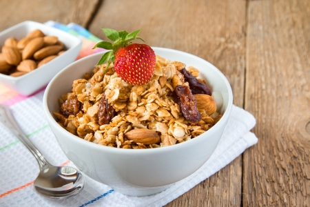 delicious and healthy wholegrain muesli breakfast, with strawberry and lots of dry fruits, nuts (almonds) and grains close up, horizontal, on wooden table with spoon Stock Photo