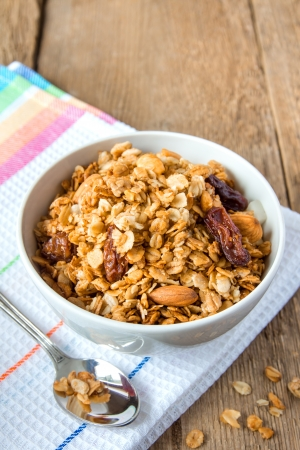 delicious and healthy wholegrain muesli breakfast, with lots of dry fruits, nuts and grains close up, vertical, on wooden table with spoon photo