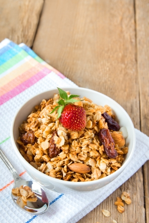 delicious and healthy wholegrain muesli breakfast, with strawberry and lots of dry fruits, nuts (almonds) and grains close up, vertical, on wooden table with spoon, copy space photo