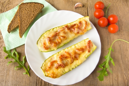 Stuffed fresh homemade zucchini with tomatoes, garlic and cheese on wooden background with argula leaves and bread, close up, horizontal, top view. Natural vegetarian dinner concept.