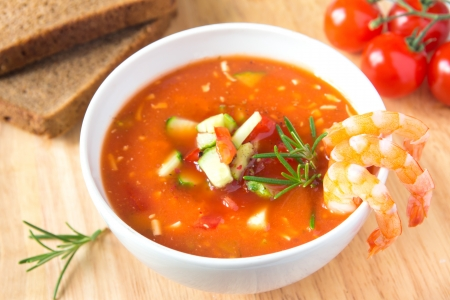 delicious tasty cold vegetable tomato soup gazpacho with shrimps and rosemary in white bowl on wooden background, closeup, horizontal Stock Photo