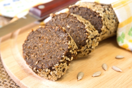 Wholegrain homemade bread with sesame close up on wooden background, horizontal photo