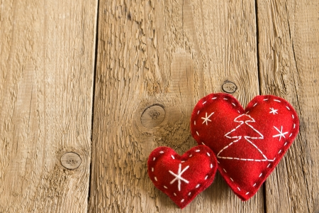 Christmas concept (decoration). Two red handmade hearts over rustic wooden (texture) close up, horizontal. photo