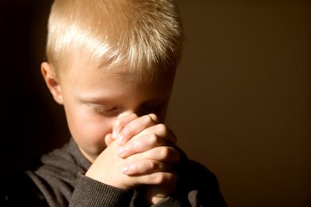 Pequeño muchacho joven y bella (niño, niño) espiritual pacífica orando y deseando, horizontal, espacio de copia.