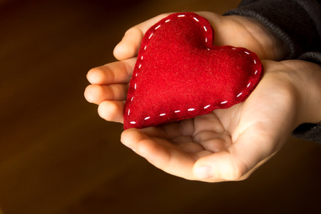 charity  symbol: Red heart in child hands, hand made gift, valentine day and family love concept, close up, horizontal