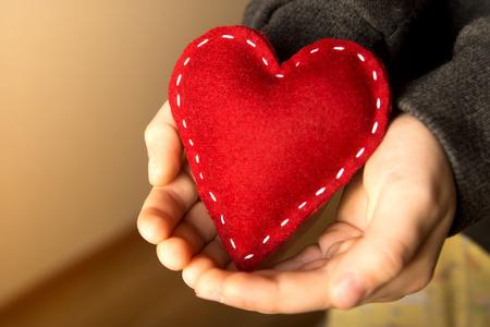 bondad: Corazón rojo en las manos del niño, regalo, hecho a mano de San Valentín, de cerca, horizontal