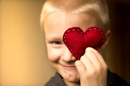 Happy cute child (kid, boy) with hand made red heart. Valentines day and family love concept. Horizontal close up portrait.