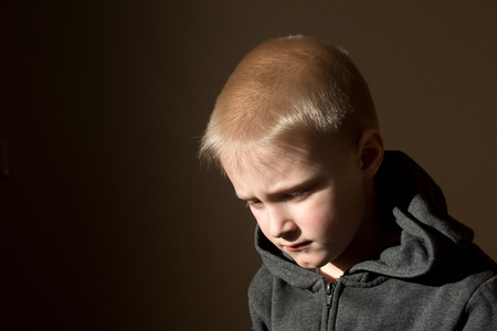 domestic life: Sad upset tired worried unhappy little child (boy) close up horizontal dark portrait with copy space