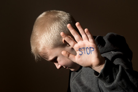 crying boy: Malestar abusado asustado niño pequeño (niño), deja de jesture mano cerca retrato oscuro horizontal con espacio de copia Foto de archivo