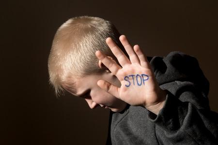 Upset misbruikt bang klein kind (jongen), stop de hand jesture close up horizontale donker portret met kopie ruimte