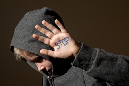 maltrato infantil: Malestar abusado asustado niño pequeño (niño), deja de jesture mano cerca retrato oscuro horizontal con espacio de copia Foto de archivo