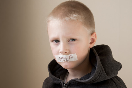 Upset abused frightened little child (boy), help, close up horizontal portrait with copy space photo