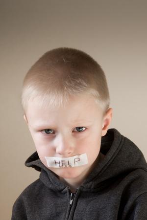 Upset abused crying frightened little child (boy), help, close up portrait with copy space photo